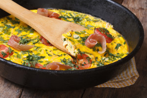 Frittata with tomato, bacon and herbs closeup in the pan with a spatula. horizontal
